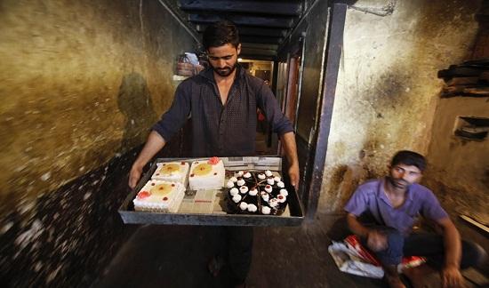 Một người thợ làm bánh ở Kashmir tấn bật chuẩn bị bánh và đi giao hàng trước ngày diễn ra Lễ hội thánh Eid-al-Fitr.