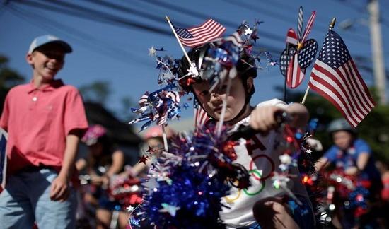 Một cậu bé lái chiếc xe đạp được trang trí rực rỡ qua ngôi làng Barnstable, Massachusetts, trong buổi diễu hành lễ kỷ niệm Quốc khánh.